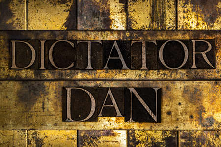 Dictator Dan text on textured grunge copper and vintage gold background Stockfoto