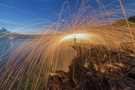 steel wool: Men cast field Fire steelwool standing on the rock at the sea sunset Stock Photo