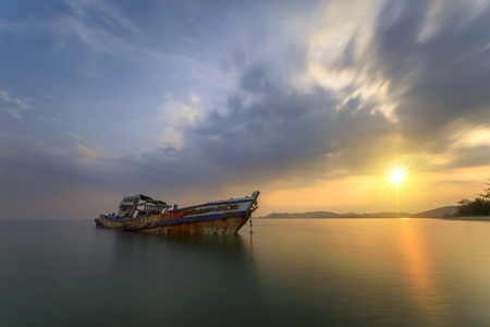 an old boat wreck at the sea of shore bank with colorful sunset