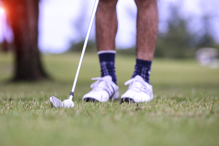 Closeup view of head iron active on man attendprepare to hitting and playing golf on grass field of outdoors background.