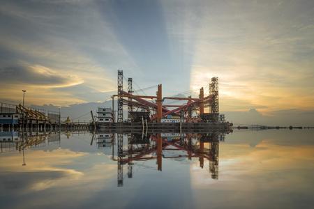 Floating crane docking in port yard at sunset background