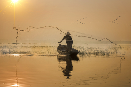 laotian: fisherman acting in throwing a net catching fish in lake morning scenery view
