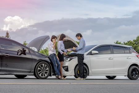O motorista da mulher pede instruções durante a revisão do agente de seguros dos danos causados pelo carro após um acidente Foto de archivo