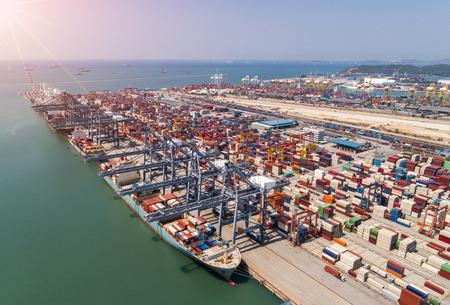 De drukte van havenbelastingen die containers laden en lossen in maritieme transporten in wereldwijde logistiek