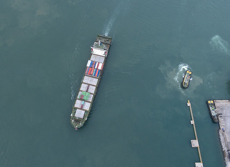 consignee: container vessel under proceeding to the entrance channel due of the port wtih tugs standing by for towage, in arial view