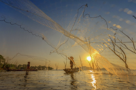 commercial fishing: fisherman in acting of throwing a nets catching fish in lake at sunset scenery view