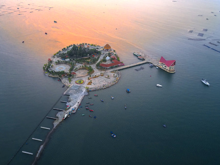 aerial view of island laying in the sea under construction of the main road entrance in sunset scenery