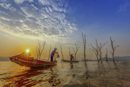 fisherman on the wooden boats, catching fish in the lake at sunset Stock Photo