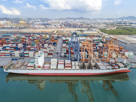 the container vessel is opening hatch cover to transition cargo of loading and discharging cargo in port alongside, aerial view