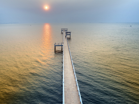 woody bay: bridge laying into the sea at sunset Stock Photo