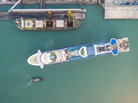 passenger cruise ship on departure un-berthing from the port terminal under pilot navigation sailing in port channel due in top view, aerial view