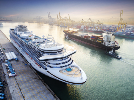 passenger ship cruise is alongside berthed the terminal in port for transit the tourist in port congestion of berth in sunrise in background, in aerial view Stock Photo