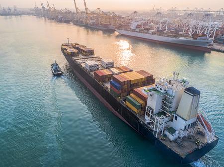포트의 안전 입구 게이트웨이에 대한 잡아 당김 보트에 의한 항구 채널에의 진행에있는 상업 선박 컨테이너 선박 스톡 콘텐츠