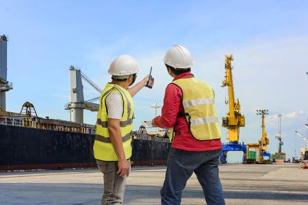 Haven- en veiligheidscontroleur die de haventerminal met de scheepswerven op de achtergrond opmeten