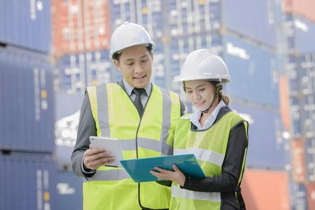 containerinspecteur die in werf met het online controleren van het controleapparaat van het communicatie apparaat werkt Stockfoto