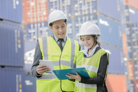 container inspector working in yard with communication device online report number checking