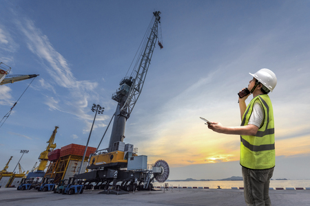 foreman take command safety instruction to the workers in terminal yard of port at sunset in background