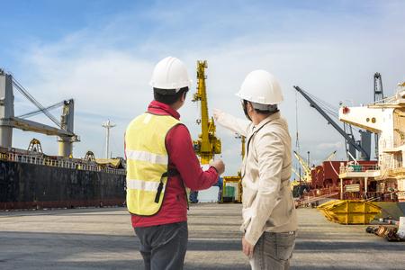 El puerto y el controler de la seguridad que examinan la terminal portuaria con el muelle de atraque del barco en fondo
