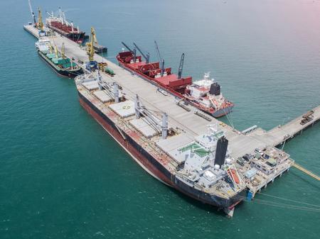 Commercieel vaartuig Algemeen vrachtschip naast de kajuit in de havenbelasting voor het laden en lossen van diensten in zeevervoer in wereldwijd logistiek in luchtfoto