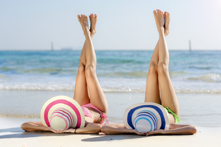 Vrouwen in bikini genieten op het strand door de benen naar de lucht te nemen Stockfoto
