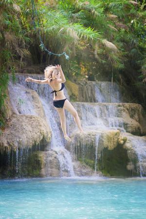 La donna gode di cascata di salto nella natura Archivio Fotografico - 77049493