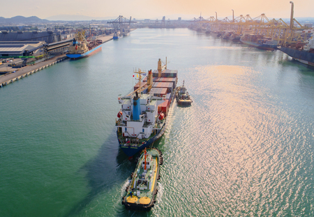 lading: container ship vessel approach to main entrance gate of the port at dawn, in aerial view
