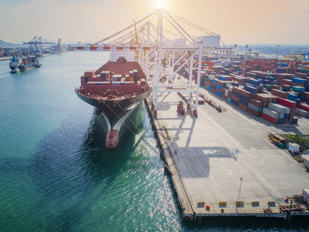 lading: container ship vessel loading and discharging operation of transhipment in international port in aerial view Stock Photo