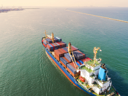 lading: container vessel ship under proceeding to the main entrance channel due of the port in aerial view