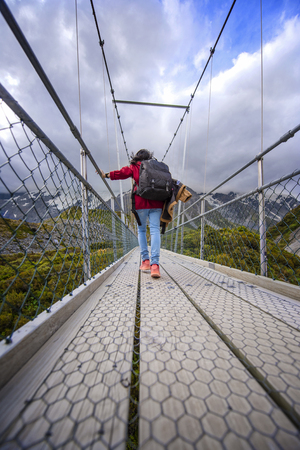 woman walking trek on the bridge over the river with mountain in background