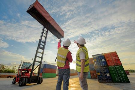 Voorman en toezichthouder werken in containerschip met heftruck stapelaar die de zending beheren