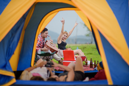 woman enjoy adventure camping by take up bottle of beer in the air cheerfully with friends playing guitar and laying inside of tent in foreground