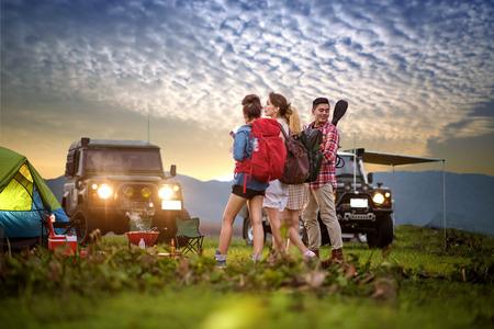 groep man en vrouw zijn vrienden genieten van kamperen picknick barbecue bij meer met zonsondergang landschap met converteerbare off-road jeep auto op achtergrond Stockfoto