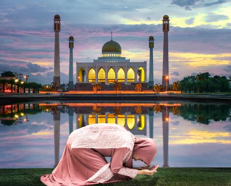 female woman muslim pray in front of mosque in Ramadan Kareem at sunset scenery