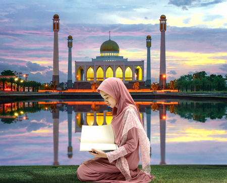 female woman muslim reading pray book in front of mosque in Ramadan Kareem at sunset scenery Stock Photo