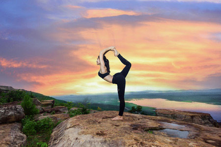 young woman practice yoga on high stage of rock with mountain and river in bottom background Stockfoto