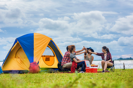 group of traveller man and woman in action of enjoyment cheerful camping near the lake at sunset