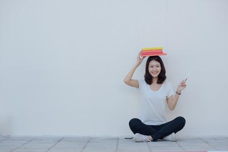 若い学生しようと頭の上に本をめくり、大学の建物の壁際の床に座って