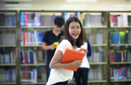 Happy Student holding a book to learning replenish in university library with colleague friends standing in background