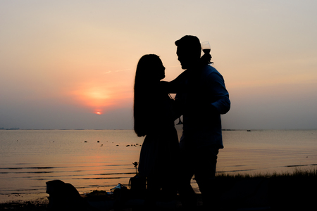 silhouette romantic couple enjoying glass of wine in a beautiful sunset at the rim of beach