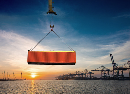 Container unit being lifting loading by the gantry crane of the port to transfer from the storage yard to the bay of the ship, with the sunset and port congestion in background Stock Photo