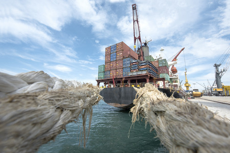 view from mooring lines attract to the after of the ship vessel loading discharging operation in port terminal for transit the cargo containers transport to the worldwide logistics system