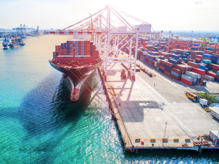 Commercial ship of container vessel in loading discharging operation in international port terminal under global services of logistics and transportation