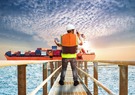surveyor inspector are in charges in yard work area at sea station for safety arrangement and inspection report on line for security and status after loading completed of container ship