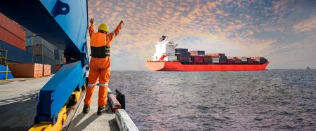 Panorama Navire porte-conteneurs quittant le terminal du port de la mer après la fin de l'opération de chargement / déchargement par un groupe d'amarres assistant à la dernière fête avec paysage au coucher du soleil en arrière-plan Banque d'images - 92175946