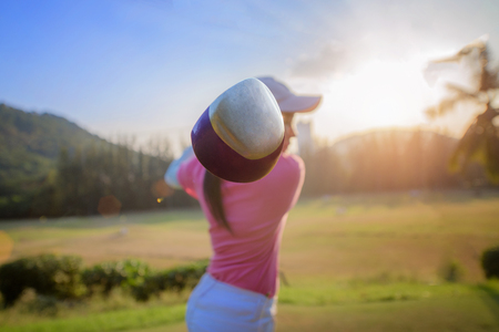 Head of wood driver at the end action of downswing of woman golf player, after hit the ball away from tees off to fairway ahead