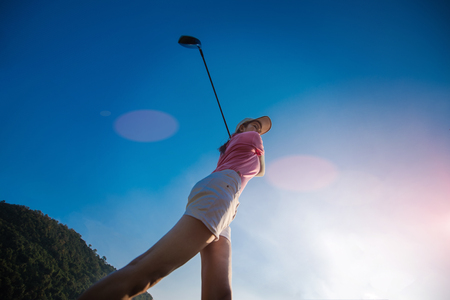 View to top of woman at the end of action downswing after hit the golf ball from tees off away to the fairway ahead Stock Photo