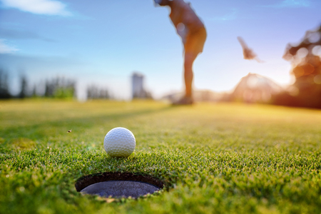 Golf ball approach to the hole on the green, putting by woman golf player in background Stock Photo