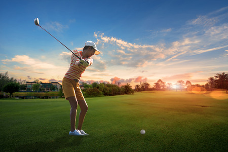 woman golf player try to hit the golf ball on nthe fairway of the golf course to the green at prospectation of best resulted, with sunrise in background