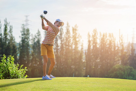 Woman golfer on tee off in attending at most back swing being to hit a ball Stock Photo