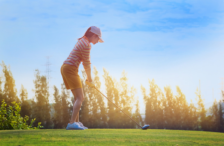 woman golfer prepare standing address on the tee off in golf course, ready to hit the ball away to the fairway ahead